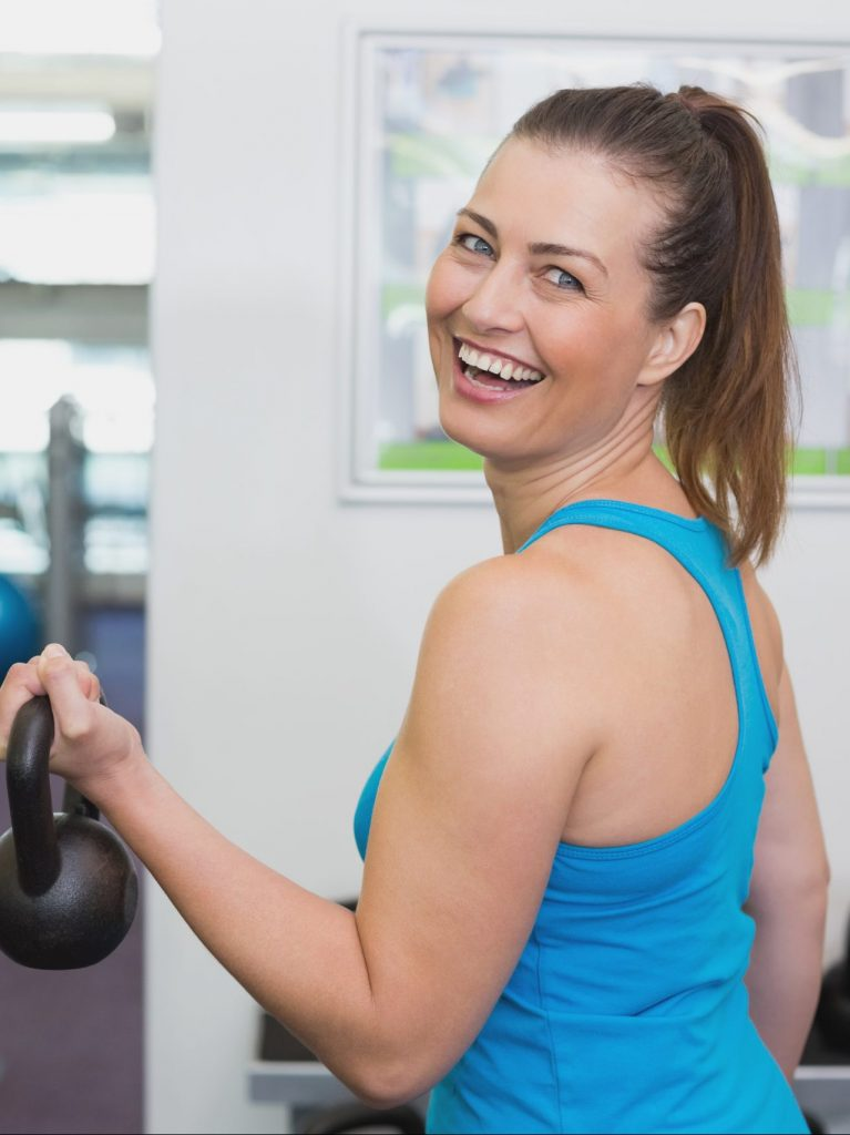 Fit Woman In 40s Holding A Kettlebell In A Gym Smiling