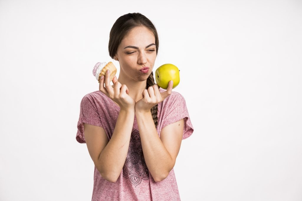 Woman Having To Choose Between A Cupcake And Apple