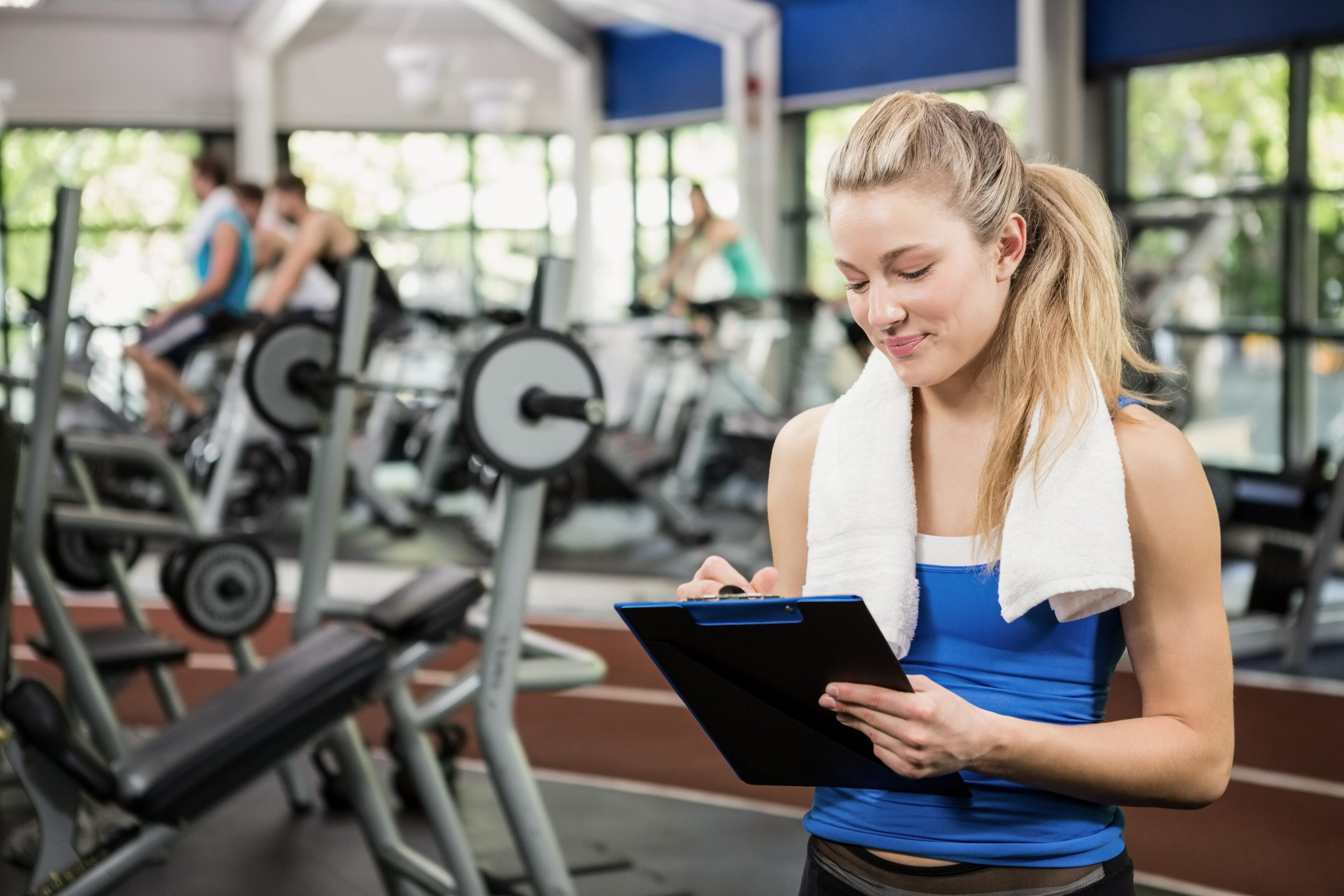 Woman writing on clipboard in weights room