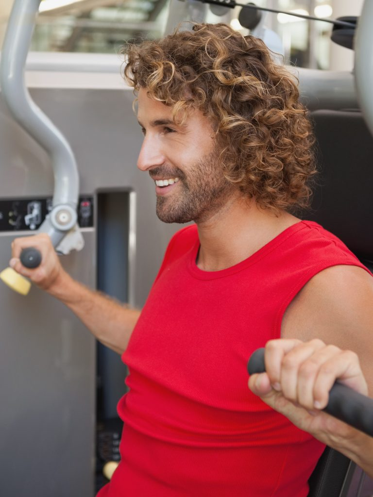 man smiling young man working on fitness machine at the gym