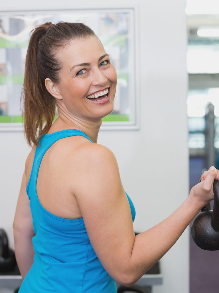 Fit brunette working out with kettlebell at the gym