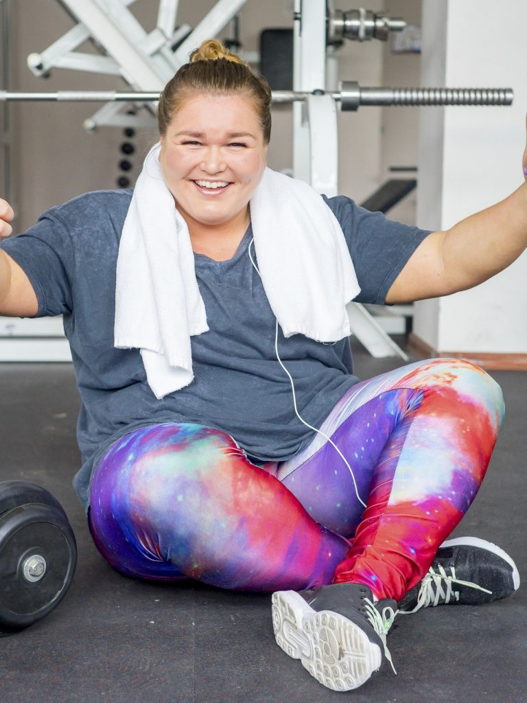 girl sitting on the floor in the gym after a session smiling