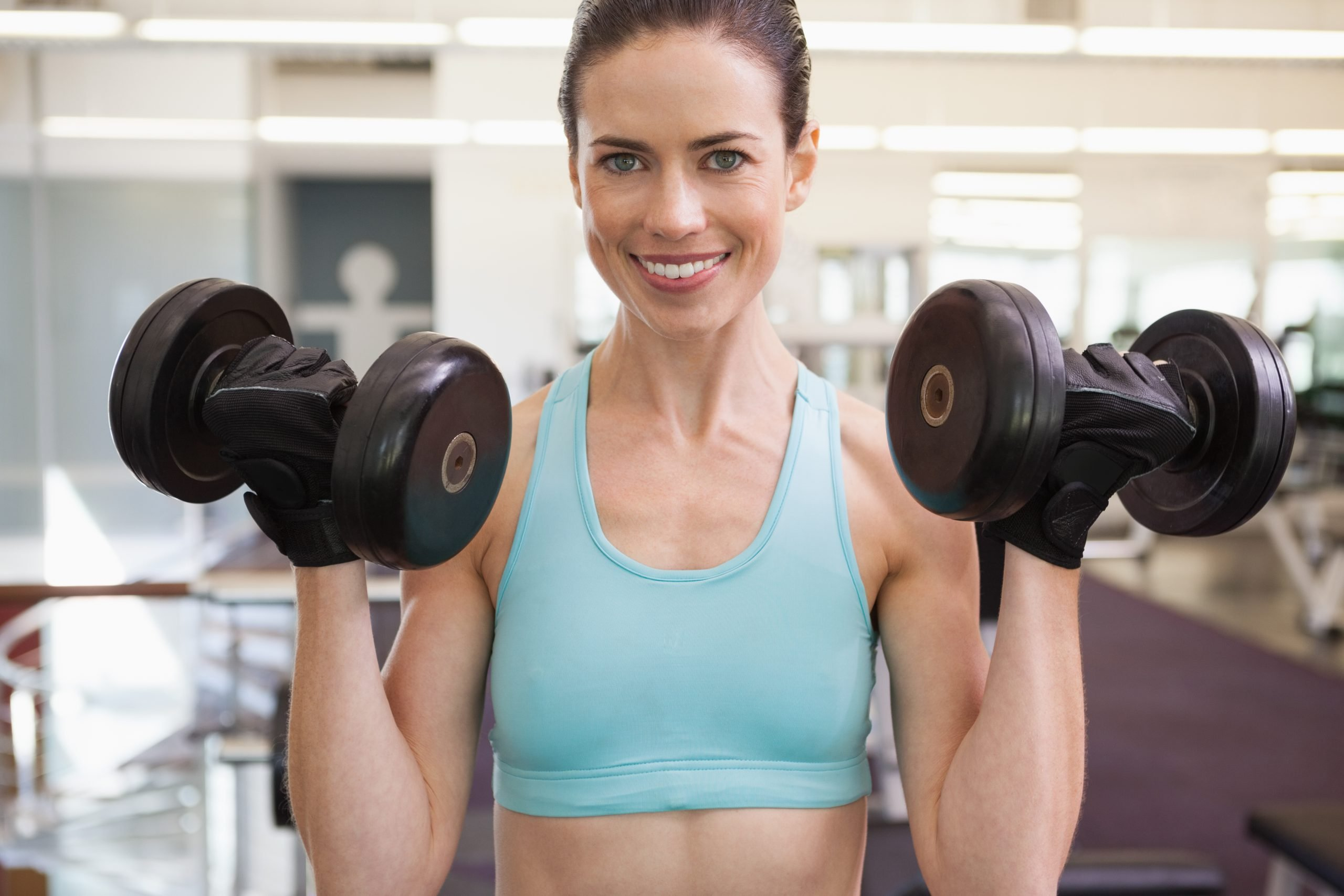 Woman-At-The-Gym-Holding-Heavy-Dumbbells-Smiling